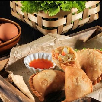 선택된 포커스 인도네시아어 파스텔 케이크는 차와 함께 하얀 접시에 제공됩니다. 카레 퍼프(karipap) 또는 jalangkote makasar로 인기