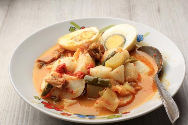 Selected focus lontong sayur padang, овощное карри с рисовым прессованным пирогом, подается с вареным яйцом