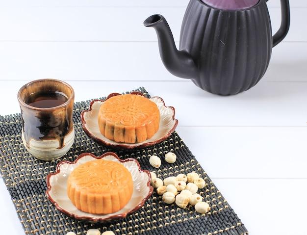 Выбранный фокус mooncake на светлом фоне с чаем. концептуальный лунный торт на фестивале середины осени или китайском новом году (имлек). лунный пирог популярный как kue bulan. подается с китайским чаем