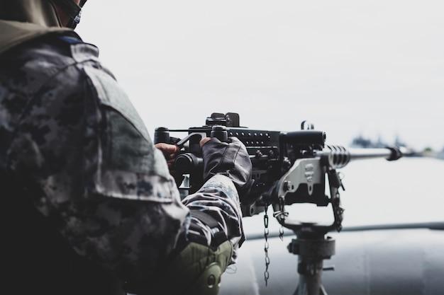 Selected focus navy soldier hand on machine gun on