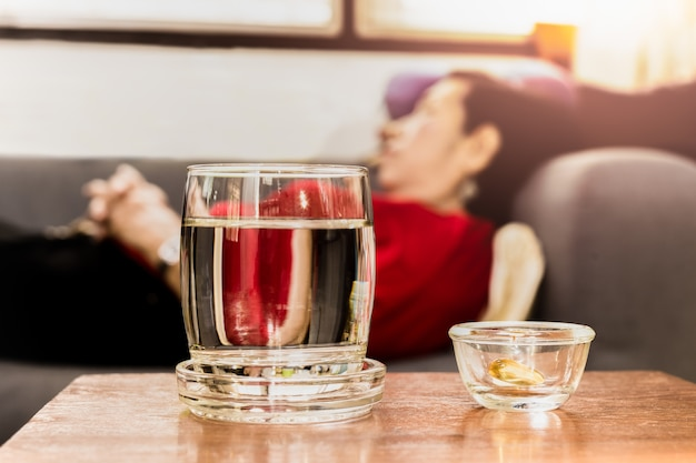 Selected focus on pills with glass of water on table with senior women sleeping