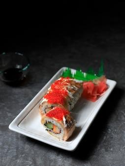 Отборный суши-ролл focus salmon blaze, крабовая палочка, огурец и жареный лосось с тобико. подается на белой прямоугольной тарелке. копировать пространство для текста