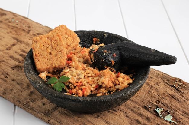 Selected focus sambal tempeh, пряный измельченный темпе на каменном пестике. традиционная индонезийская кухня с острым и пикантным вкусом