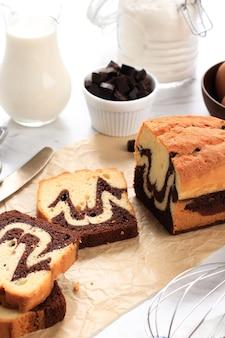 白い背景の茶色のベーキングペーパー上の自家製マーブルケーキの選択されたフォーカススライス
