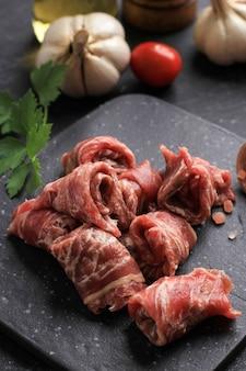 Отборный рулет с тонкими ломтиками для японской кухни: сябу-сябу, гюдон, горячий горшок или нику удон. подается на черной тарелке