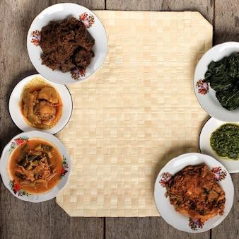 パダンレストランの厳選されたフォーカス様々なメニュー。中央にコピースペースがある素朴な背景の自家製マサカンパダンまたはミナン料理。