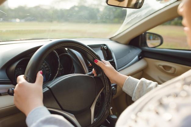 선택된 초점 여자는 자동차의 핸들에 손입니다