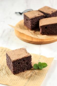 厳選されたフークスブラックもち米シフォンケーキ。黒もち米粉を使用した、柔らかくしっとりとしたスライスケーキ。白いテーブルでお召し上がりいただけます。テキスト用のスペースをコピーします。