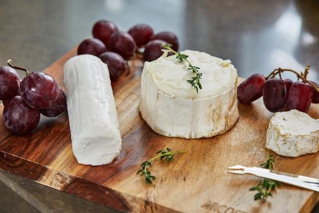 Отборные французские сыры с виноградом, на деревянной доске с розмарином и ножом.