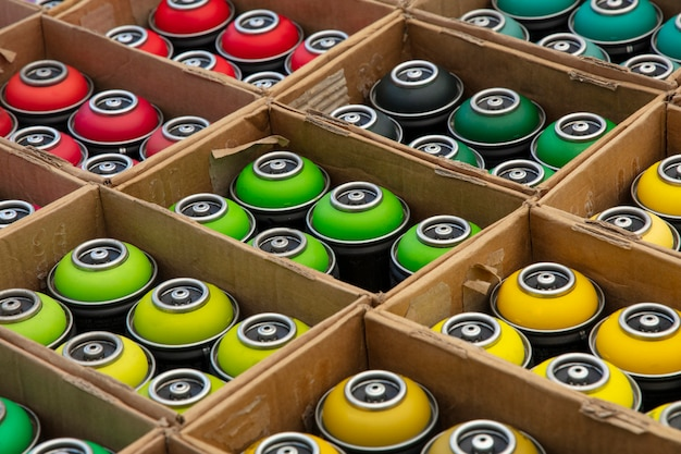Selection of assorted colors graffiti spray paint cans in cardboard boxes
