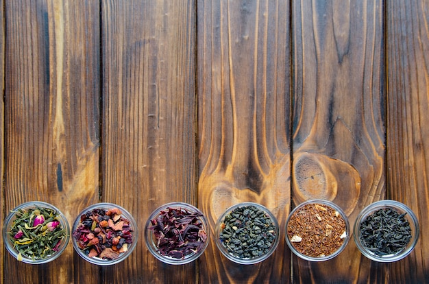 Selection of assorted teas in transparent little bowls on natural wood
