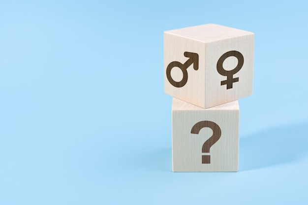 Selection or changing gender concept.hand turns cube with male and female icons over cube with question icon