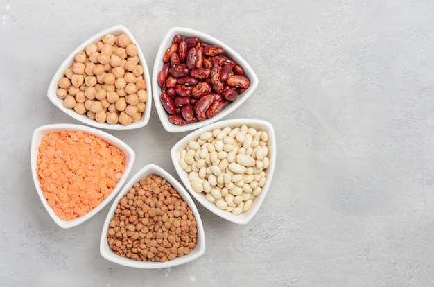 Selection of dry legumes, lentils and peas in white bowls on gray concrete background.