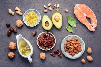 Selection food sources of omega 3 and unsaturated fats on dark stone background.