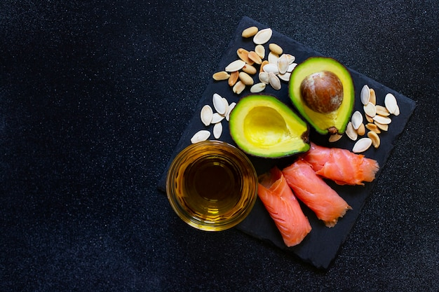 Selection of healthy fat sources, avocado, salmon, nuts, olive oil on a black plate. the concept of healthy eating. top view, copy space, black background