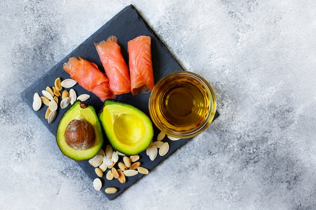 Selection of healthy fat sources, avocado, salmon, nuts, olive oil on a black plate. the concept of healthy eating. top view, copy space, gray background