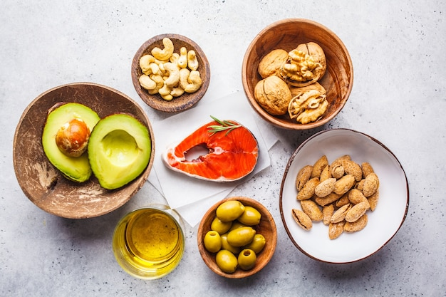 Selection of healthy fat sources: fish, nuts, oil, olives, avocado on white surface, copy space
