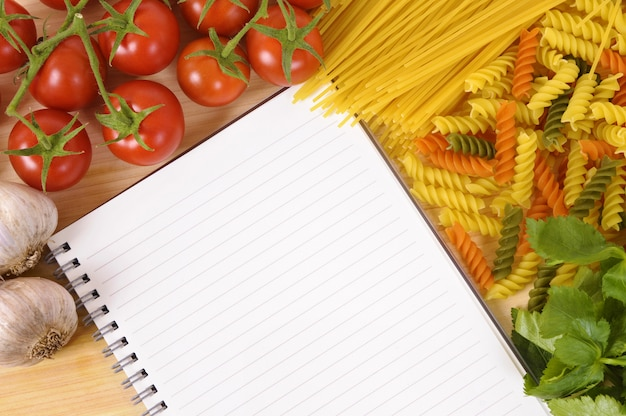 Selection of italian spaghetti and pasta with blank recipe book or cookbook.