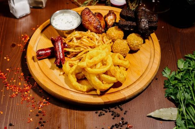Выбор пива и закусок. чипсы, рыба, пивные колбаски на столе