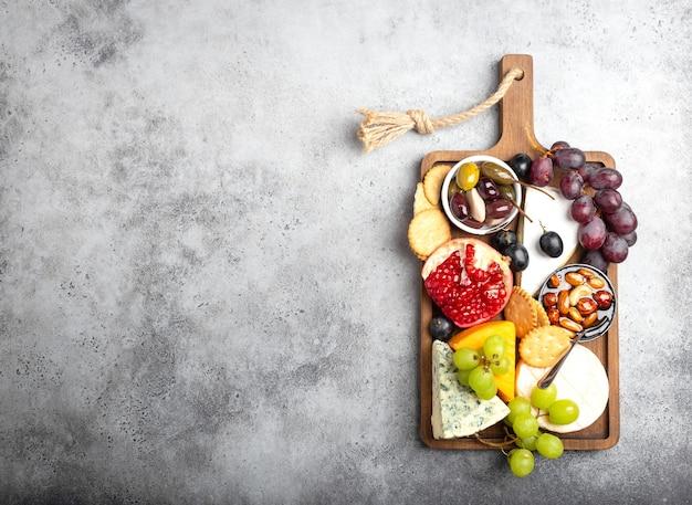 치즈와 전채, 카망베르, 브리, 체다, 빵, 크래커, 포도, 견과류, 꿀 선택. 텍스트, 위쪽 전망, 클로즈업을 위한 공간이 있는 소박한 나무 보드에 다양한 치즈 혼합