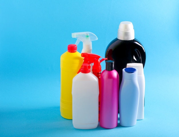 Выбор красочных пластиковых бутылок, используемых дома на синем фоне