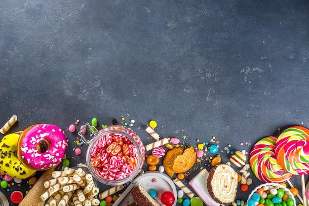 다채로운 과자 선택. 검은 콘크리트 배경에 다양 한 사탕, 초콜릿, 도넛, 쿠키, 막대 사탕, 아이스크림 평면도 세트