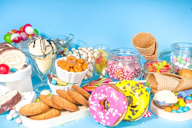 다채로운 과자 선택. 다양 한 사탕, 초콜릿, 도넛, 쿠키, 막대 사탕, 유행 밝은 파란색 밝은 배경에 아이스크림 평면도 세트