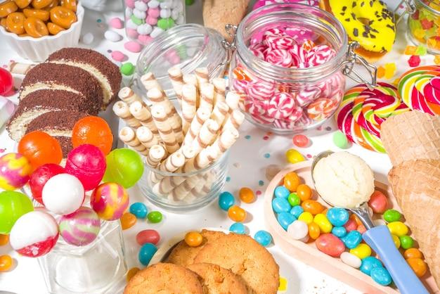 色とりどりのスイーツセレクション。白い背景にさまざまなキャンディー、チョコレート、ドーナツ、クッキー、ロリポップ、アイスクリームのトップビューのセット