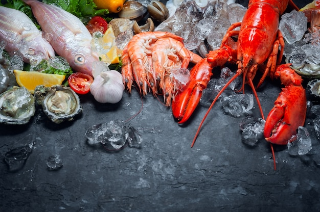新鮮なロブスター、エビ、魚、カキ、イカ、カニのレモンとアイスキューブの選択