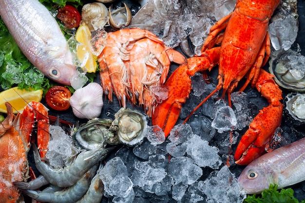 Выбор свежих лобстеров, креветок, рыбы, устриц, кальмаров и крабов с лимоном и кубиками льда.
