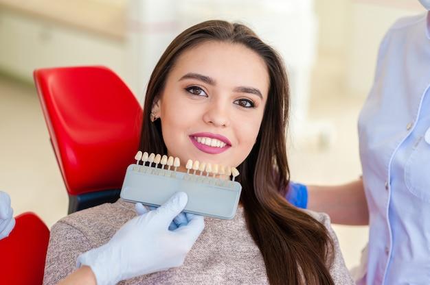 Подбор цвета зубов красивой девушке в стоматологии.