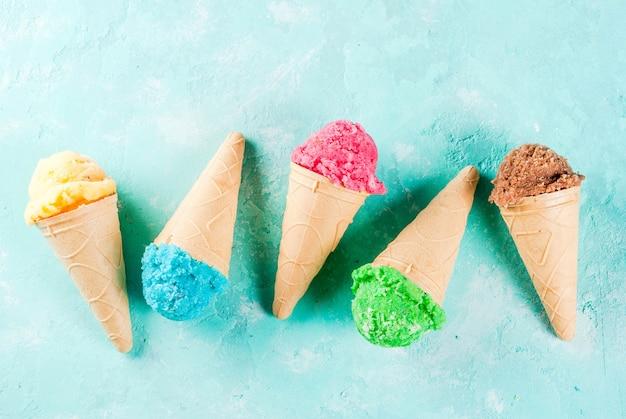 아이스크림 콘에 다양한 밝은 여러 가지 아이스크림 선택-초콜렛 바닐라 블루 베리 딸기 피스타치오 오렌지, 밝은 파란색 맑은 표면에 복사 공간 평면도