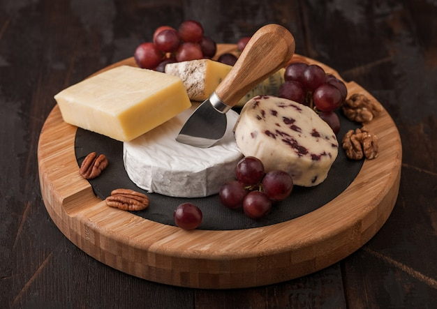 ボード上のさまざまなチーズと木製のテーブルの背景にブドウの選択。丸まな板にナイフでブルースティルトン、レッドレスター、ブリーチーズ。