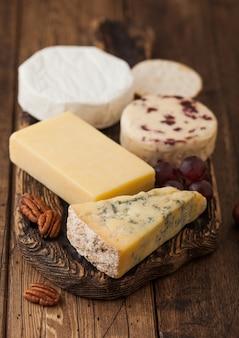 木製の背景のボード上の様々なチーズの選択。ヴィンテージまな板にブルースティルトン、レッドレスター、ブリーチーズ。