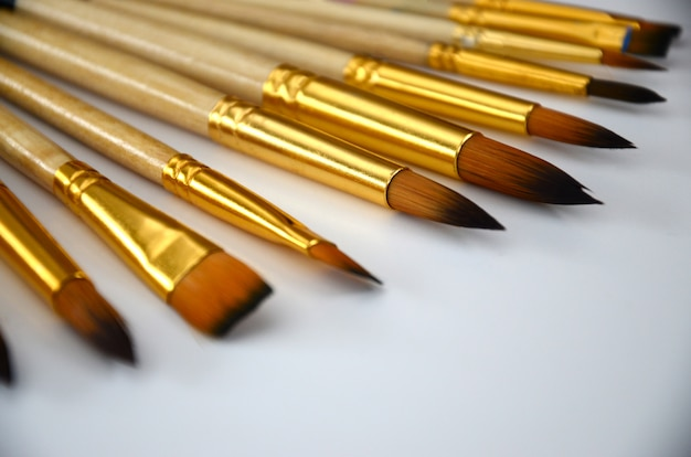 A selection of orange brushes with different sizes on a white surface