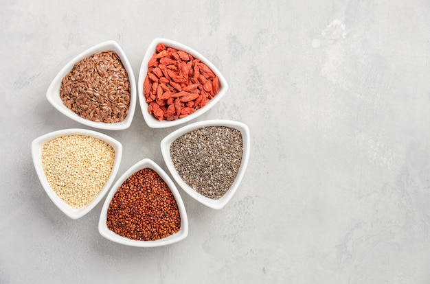 Selection of super foods in white bowls on gray concrete background.