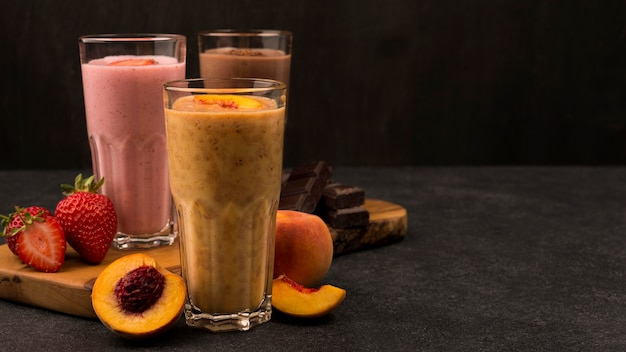 Selection of three milkshake glasses with chocolate and fruits