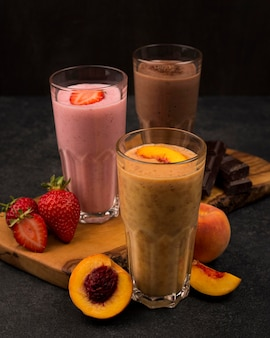 Selection of three milkshake glasses with fruits and chocolate