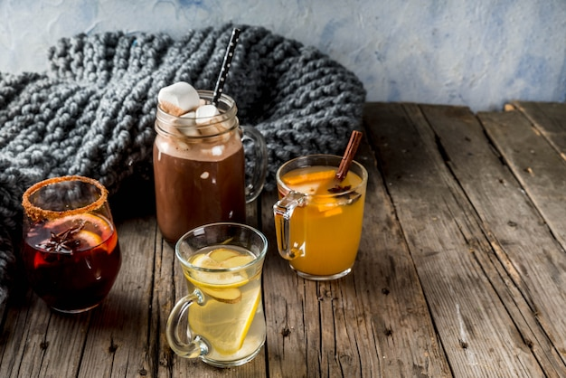 Selection of various autumn traditional drinks: hot chocolate with marshmallow, tea with lemon and ginger,