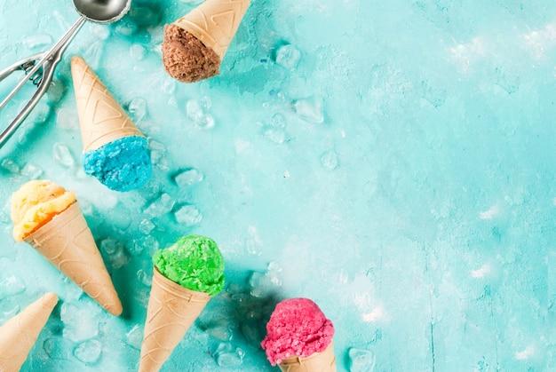 Selection of various bright multicolored icecream in ice cream cones chocolate vanilla blueberry strawberry pistachio orange on light blue sunny background top view