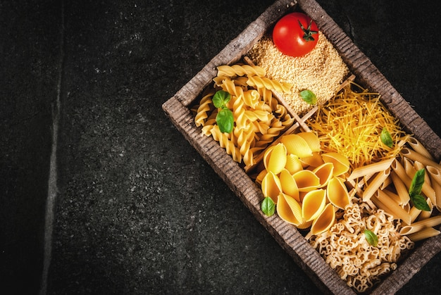 Selection of various raw italian pasta with basil leaves and cherry tomato, in old wooden box on dark stone table, top view