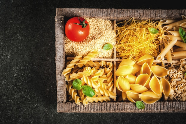 Selection of various raw italian pasta with basil leaves and cherry tomato in old wooden box on dark stone table