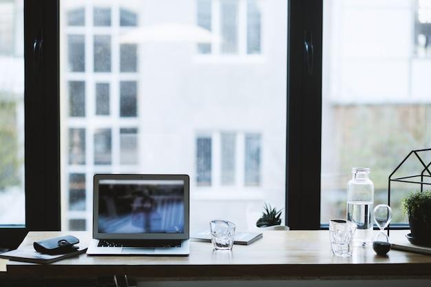 灰色のラップトップとテーブルの上のガラスの近くの雑誌に黒い財布の選択的なクローズアップショット