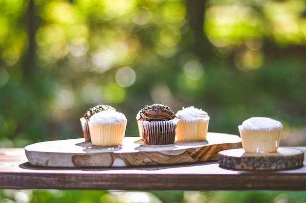 나무 표면에 초콜릿과 크림 컵 케이크의 선택적 근접 촬영 샷