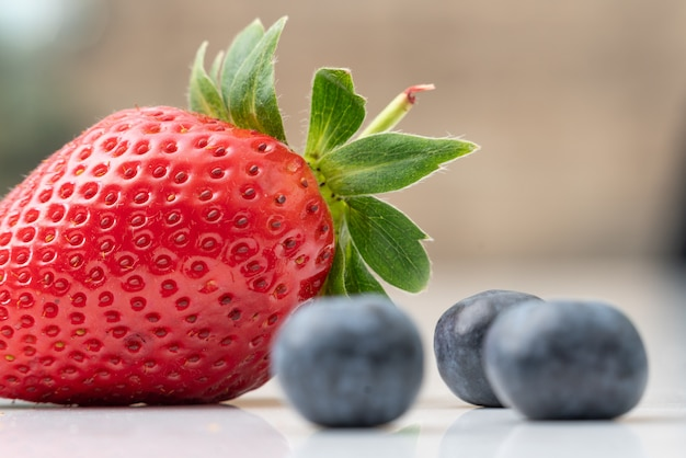 Selective closeup shot of ripe strawberry and blueberries