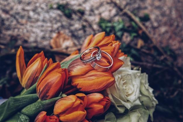 Colpo selettivo del primo piano degli anelli di diamante d'argento sui tulipani arancioni e sulle rose bianche