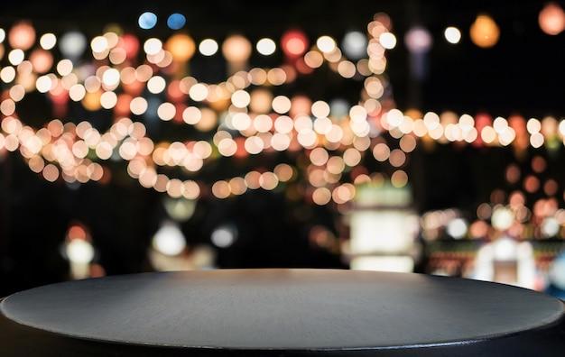 光スポットとボケ味を持つ抽象的なぼやけたお祭りの明るい背景の前に選択的な空の木製テーブル