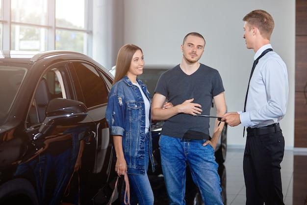 選択的な焦点自動車販売店マネージャーは、自動車販売店のカップルに高級車を見せます