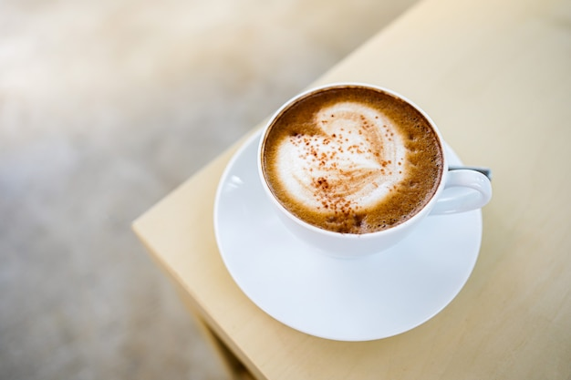 セレクティブフォーカス、木製のテーブルに美しいミルクフォームラテアートの質感を持つホットラテコーヒーのカップ。