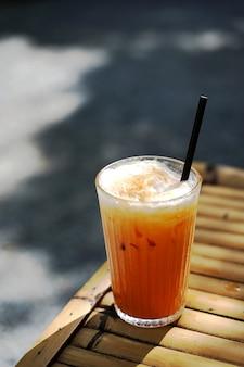新鮮な牛乳を注ぐお茶と牛乳の層を備えたタイのオレンジミルクティーのグラスにセレクティブフォーカス